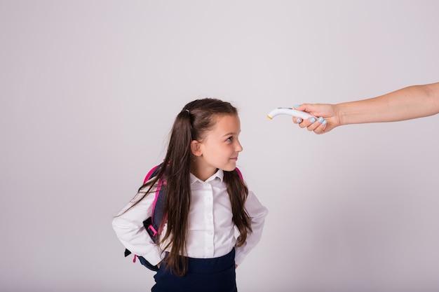 Une écolière brune en uniforme et avec un sac à dos mesure la température avec un thermomètre infrarouge sur fond blanc avec une place pour le texte