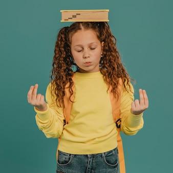 Écolière avec chemise jaune tenant un livre sur la tête