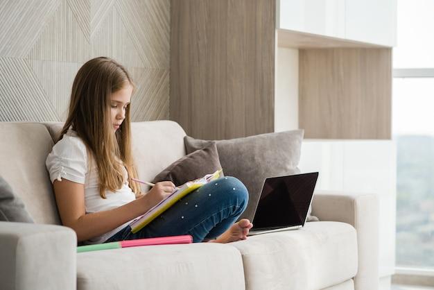 Une écolière ciblée étudie sur un canapé avec un ordinateur