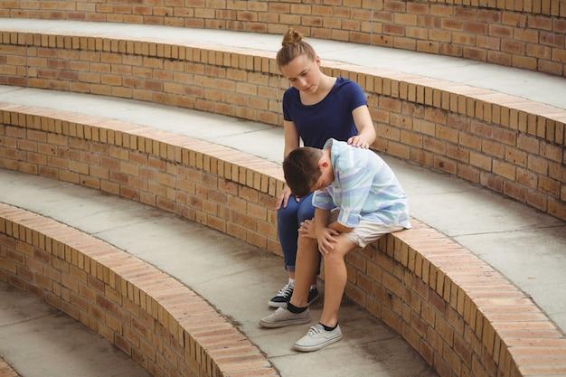 Écolière consolant son amie triste sur les marches du campus