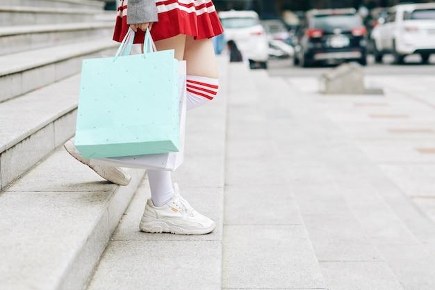 Une écolière coréenne quittant le centre commercial avec des sacs à provisions dans les mains