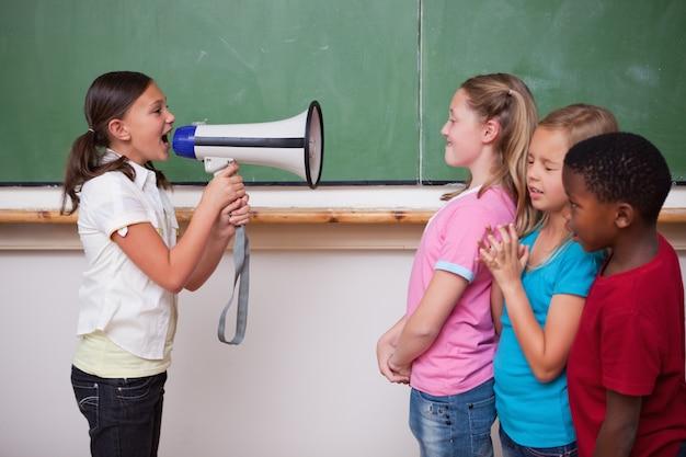 Écolière crier à travers un mégaphone à ses camarades de classe