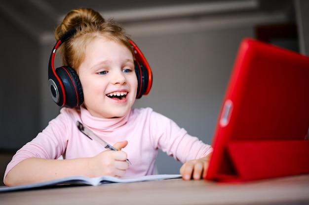 Écolière dans les écouteurs étudie à la maison avec tablette numérique, souriant et fait ses devoirs scolaires.