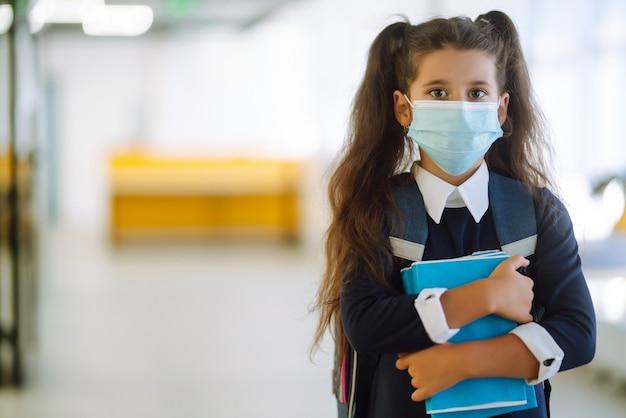 Écolière dans un masque de protection avec un sac à dos et un manuel.