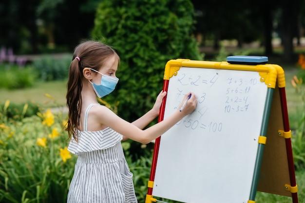 Une écolière dans un masque se lève et écrit des leçons sur le tableau noir