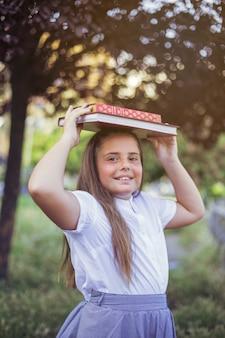 Écolière debout avec des livres sur la tête en souriant
