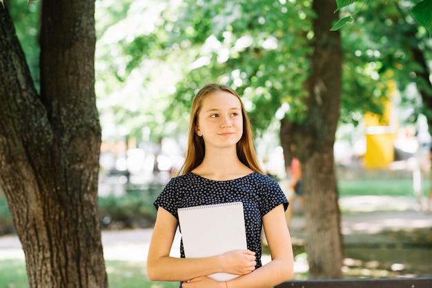 Une écolière diligente posant avec un bloc-notes