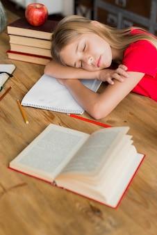 Écolière dormir au milieu de manuels scolaires
