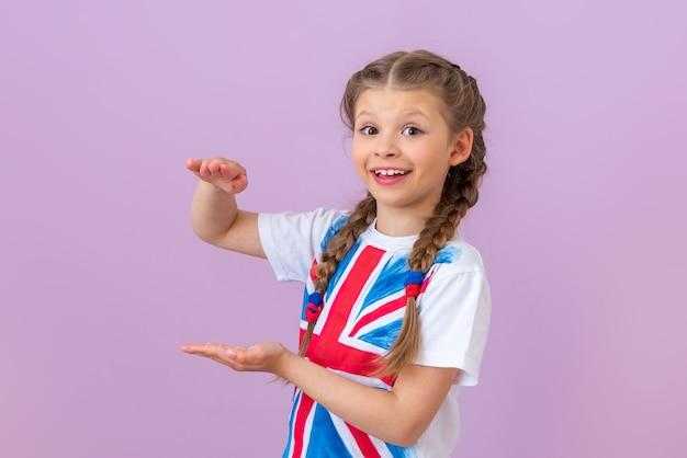 Une écolière avec le drapeau de la grande-bretagne sur son t-shirt montre deux mains et sourit.