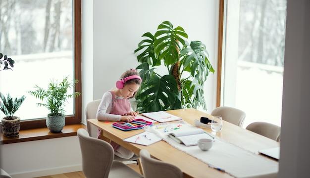 Écolière avec des écouteurs assis et travaillant à table à l'intérieur à la maison, apprentissage à distance.