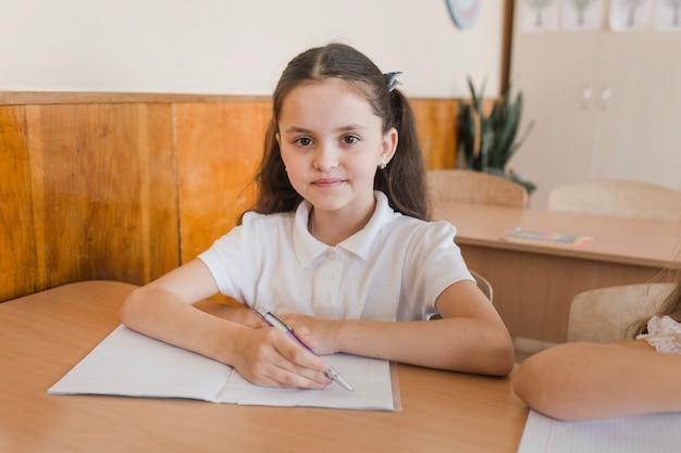 Écolière écrivant et regardant la caméra