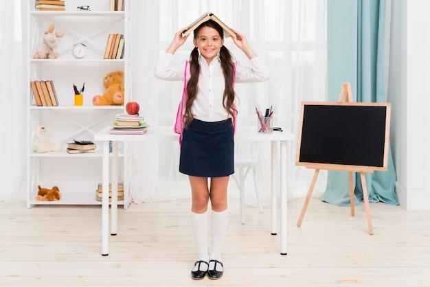 Écolière ethnique, debout, sous, toit livre