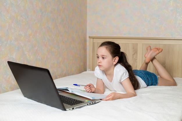 Écolière étudie à la maison avec un ordinateur portable tablette numérique et fait ses devoirs d'école sur le lit avec des livres de formation