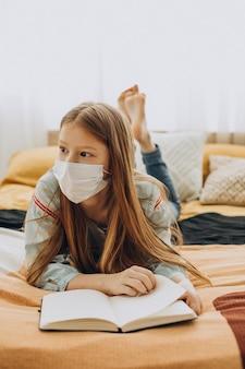 Écolière étudie à la maison portant un masque, apprentissage à distance