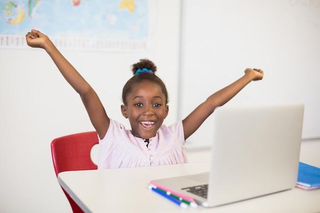 Écolière excitée avec ordinateur portable en classe