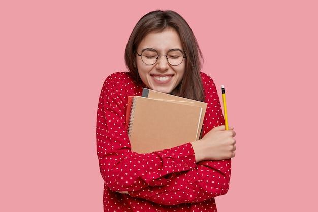 Écolière avec expression positive porte cahier étroitement à elle-même, sourit largement, tient un crayon, porte une chemise rouge à la mode, isolée sur fond rose