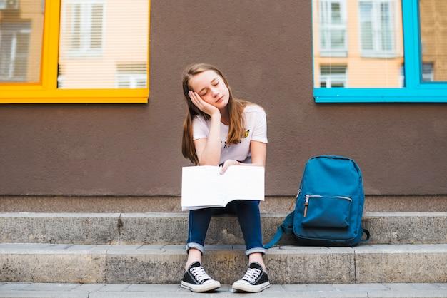 Écolière fatiguée avec bloc-note à la rue
