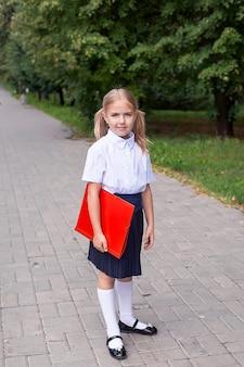 Écolière-fille élégante marchant dans le parc, concept d'apprentissage. uniforme scolaire. 1er septembre