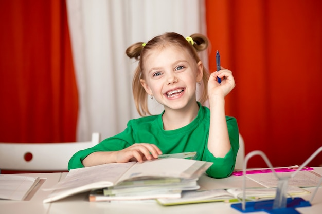 Écolière fille heureuse à faire leurs devoirs sur fond rouge