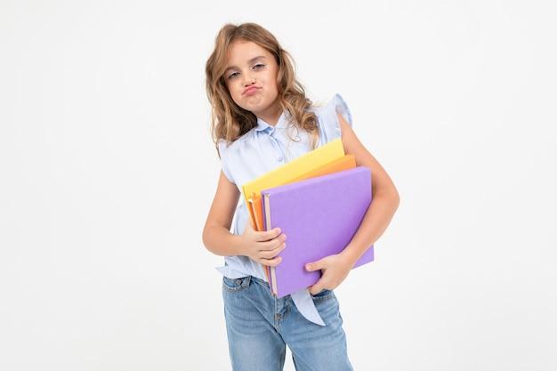 Écolière fille avec une montagne de livres pour la connaissance isolé sur fond blanc avec espace de copie.