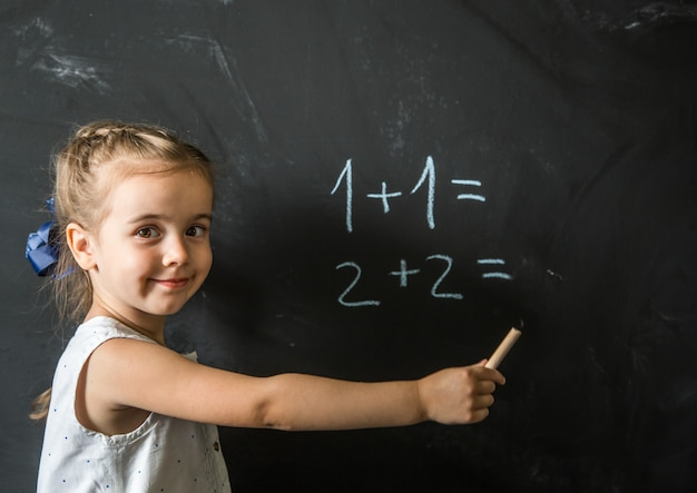 Écolière de fille près de tableau noir