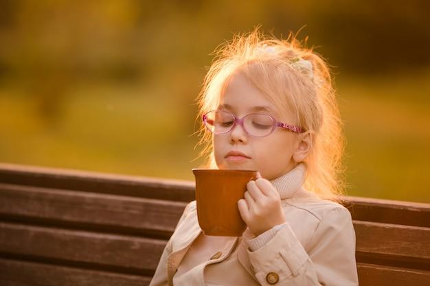 Écolière frisée dans les verres et manteau léger avec une grande tasse de cacao chaud dans le parc en automne