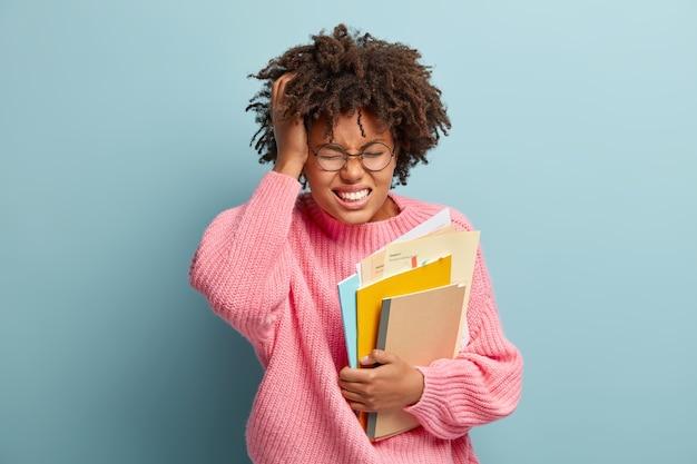 Une écolière frustrée a de terribles maux de tête, fronce les sourcils face à la douleur, étudie bien, tient le journal avec des papiers, porte des lunettes optiques rondes et un pull rose, se tient au-dessus du mur bleu, triste d'oublier le test
