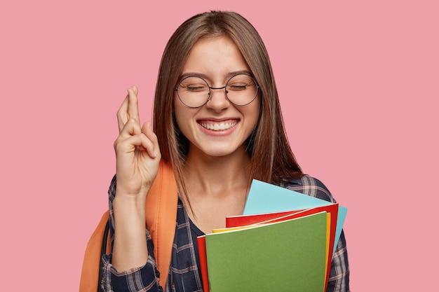 Écolière gaie intense avec un large sourire, croise les doigts pour la bonne chance, a une expression satisfaite, garde les yeux fermés, porte un sac à dos,