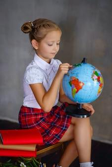 Écolière avec globe terrestre. concept d'école