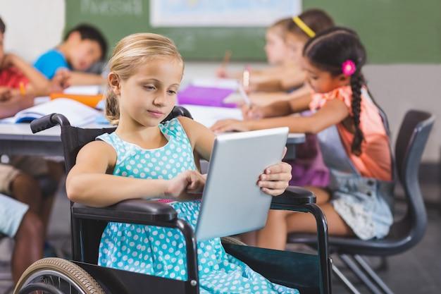 Écolière handicapée à l'aide d'une tablette numérique