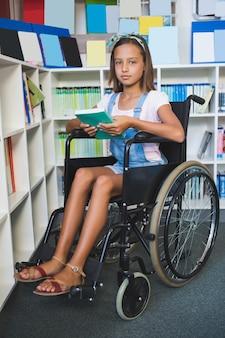 Écolière handicapée en fauteuil roulant tenant un livre dans la bibliothèque