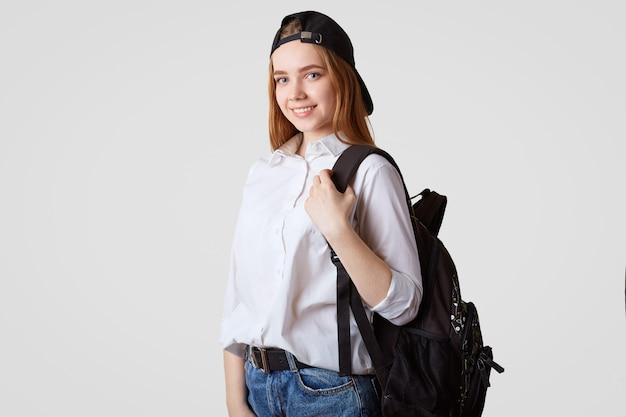 Écolière heureuse en casquette noire et chemise blanche, porte un sac à dos avec des livres, prêt à commencer une nouvelle année d'études, pose sur blanc. un étudiant revient à la maison après ses cours