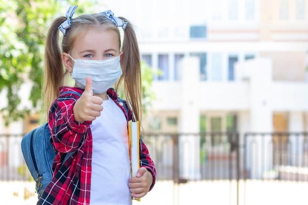 Écolière heureuse dans un masque de protection avec un sac à dos