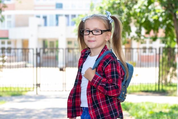Écolière heureuse avec des lunettes dans la rue