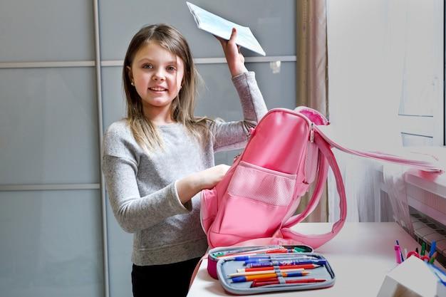 Une écolière heureuse à la maison va à l'école l'enfant ramassant un sac à dos à l'école