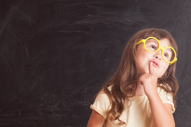 Écolière heureuse de petite fille du tableau noir