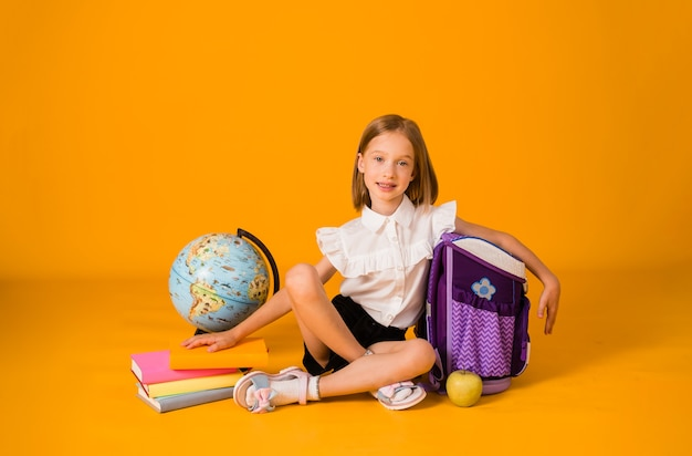 Une écolière heureuse en uniforme est assise avec des fournitures scolaires et un globe sur fond jaune avec une copie de l'espace