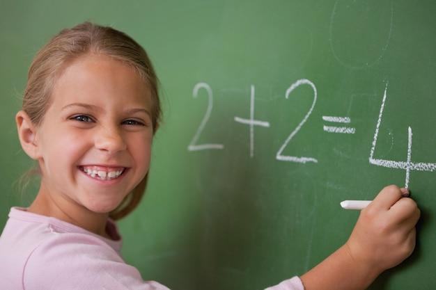 Écolière heureux écrivant un nombre