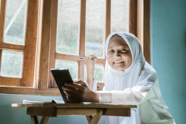 Écolière indonésienne étudie ses devoirs pendant sa leçon en ligne à la maison