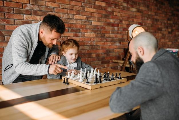 Écolière intelligente jouant aux échecs avec l'homme.