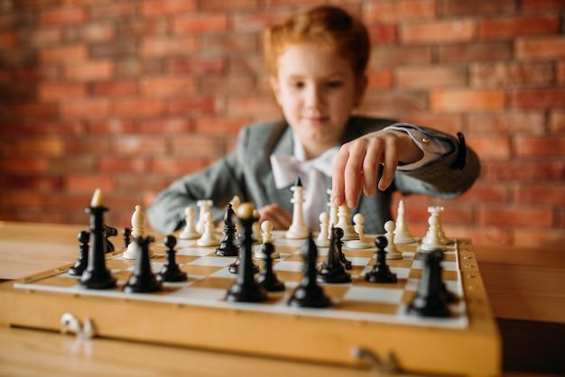 Écolière intelligente, joueur d'échecs à la table