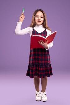 Écolière intelligente avec livre et stylo