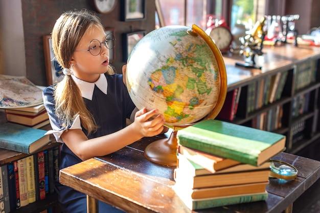 Une écolière intelligente avec des lunettes regarde le globe avec surprise