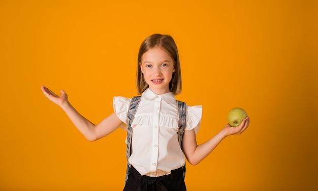 Une écolière intelligente en uniforme et avec un sac à dos tient une pomme sur fond jaune avec une place pour le texte.
