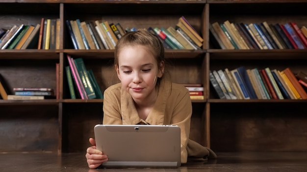 Une écolière intéressée joue à un jeu en ligne sur une tablette dans la bibliothèque