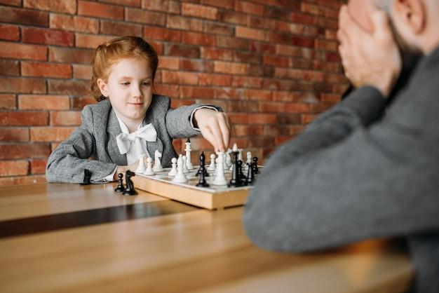 Écolière jouant aux échecs avec une personne de sexe masculin adulte
