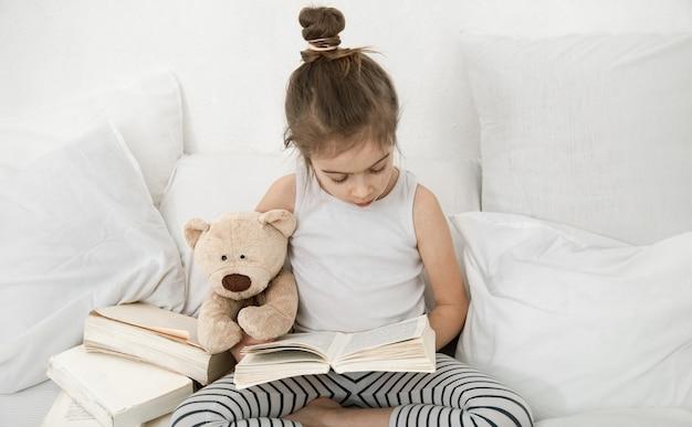 Écolière lit un livre en pyjama au lit avec un ours en peluche. le concept de développement de l'enfant et de développement personnel.