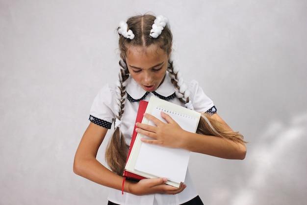 Une écolière avec des livres dans ses mains