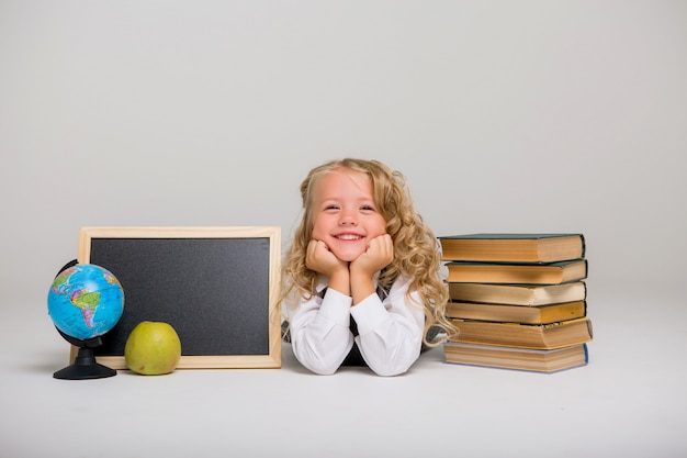 Écolière avec des livres sur un fond clair