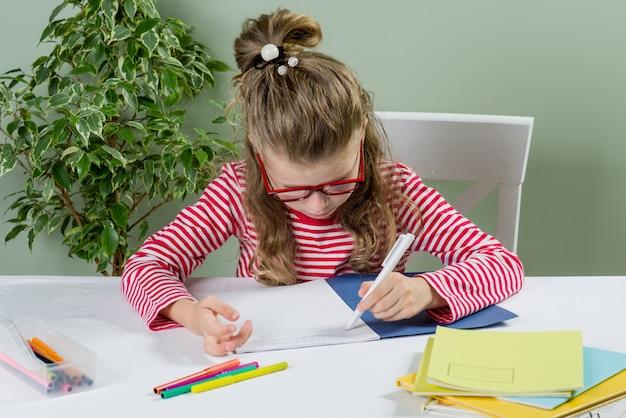 Écolière à lunettes écrit quelque chose